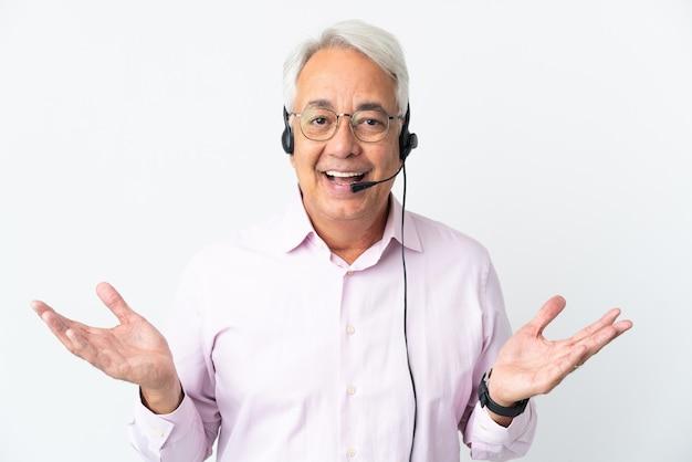 Operador de telemarketing homem de meia-idade trabalhando com um fone de ouvido isolado no fundo branco com expressão facial chocada