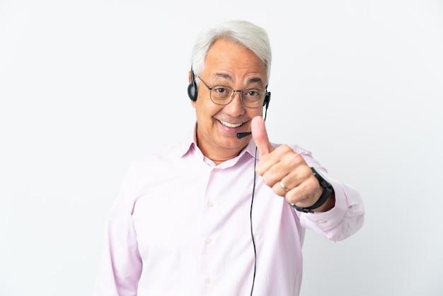 Operador de telemarketing homem de meia-idade trabalhando com um fone de ouvido isolado no fundo branco com o polegar para cima porque algo bom aconteceu
