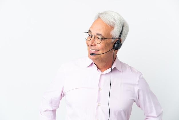 Operador de telemarketing homem de meia-idade trabalhando com um fone de ouvido isolado no fundo branco, olhando para o lado e sorrindo