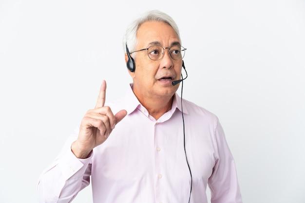 Operador de telemarketing homem de meia idade trabalhando com um fone de ouvido isolado no fundo branco, tendo uma ideia apontando o dedo para cima