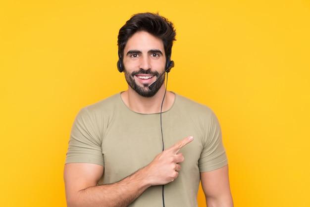 Operador de telemarketing homem trabalhando com um fone de ouvido sobre parede amarela isolada, apontando o dedo para o lado
