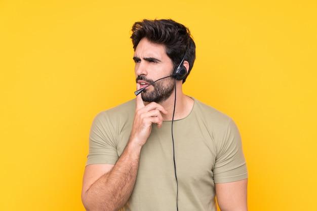 Operador de telemarketing homem trabalhando com um fone de ouvido sobre parede amarela isolada, pensando uma idéia