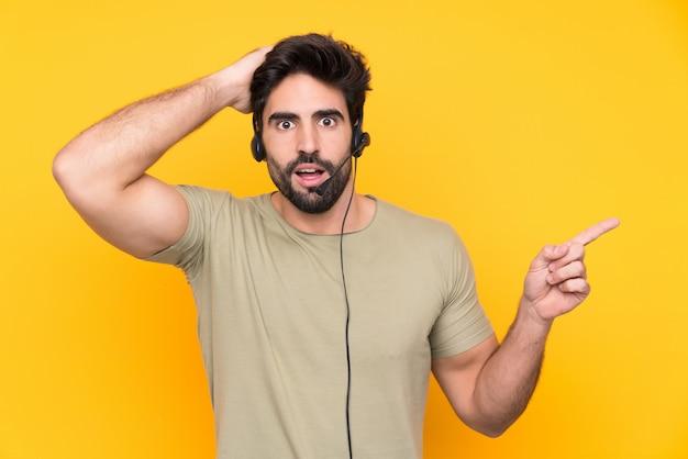 Operador de telemarketing homem trabalhando com um fone de ouvido sobre parede amarela isolada surpreendeu e apontando o dedo para o lado