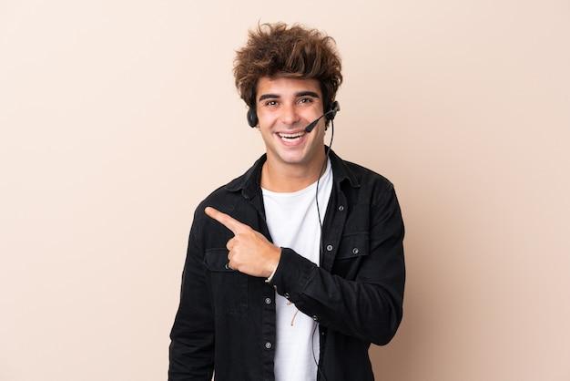 Operador de telemarketing homem trabalhando com um fone de ouvido sobre parede isolada, apontando o dedo para o lado