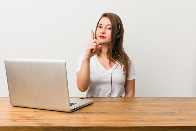 Operador de telemarketing jovem mostrando o número um com o dedo