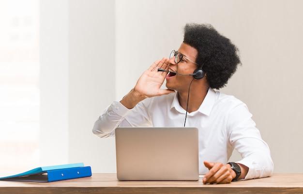 Operador de telemarketing jovem negro sussurrando fofoca