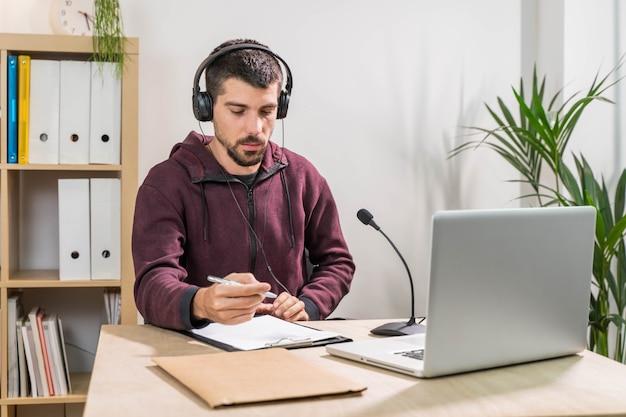 Operador de telemarketing ou podcast trabalhando com um laptop e falando em um fone de ouvido com máscara facial no escritório