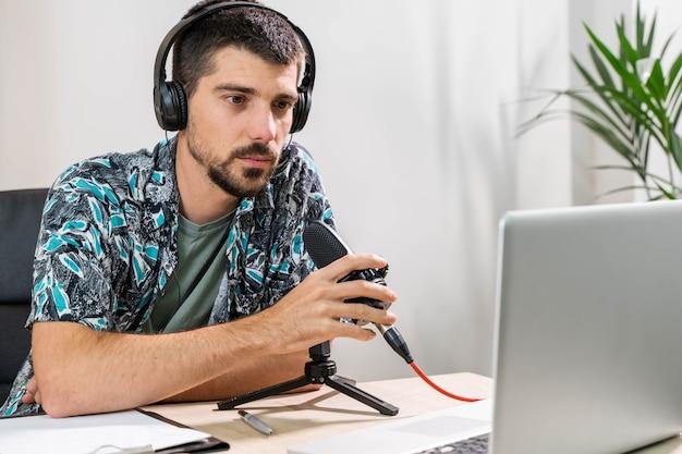 Operador de telemarketing ou podcast trabalhando com um laptop e falando em um fone de ouvido no escritório do estúdio