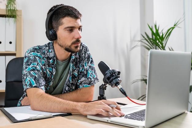 Operador de telemarketing ou podcast trabalhando com um laptop e falando em um fone de ouvido no escritório
