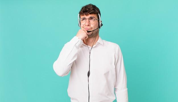Operador de telemarketing pensando, sentindo-se em dúvida e confuso, com opções diferentes, imaginando qual decisão tomar