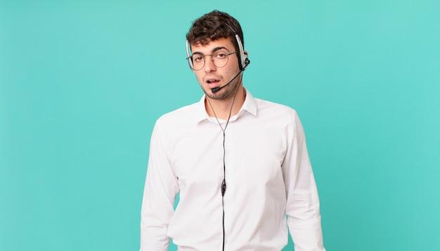 Operador de telemarketing perplexo e confuso, com uma expressão muda e atordoada olhando para algo inesperado