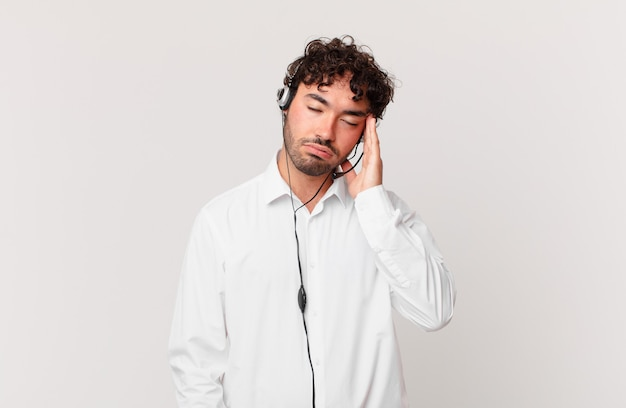 Operador de telemarketing se sentindo entediado, frustrado e com sono após uma tarefa cansativa, enfadonha e tediosa, segurando o rosto com a mão