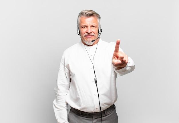 Operador de telemarketing sênior sorrindo e parecendo amigável, mostrando o número um ou o primeiro com a mão para a frente, em contagem regressiva
