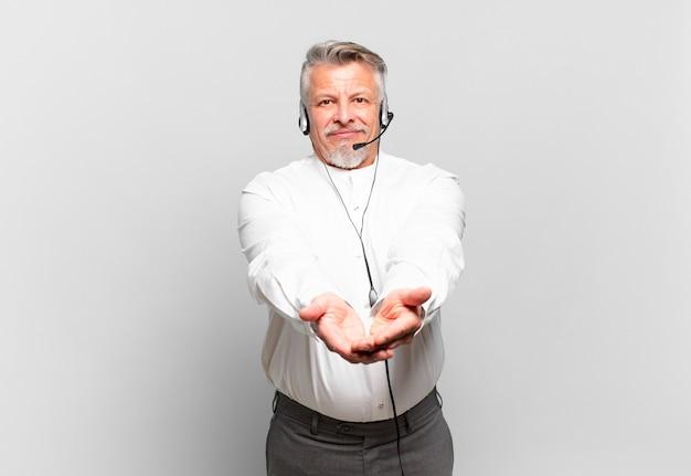 Operador de telemarketing sênior sorrindo feliz com um olhar amigável, confiante e positivo, oferecendo e mostrando um objeto ou conceito