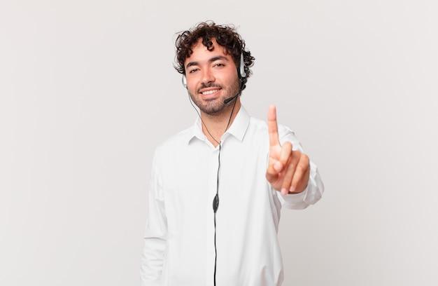 Operador de telemarketing sorrindo com orgulho e confiança fazendo a pose número um triunfantemente, sentindo-se um líder