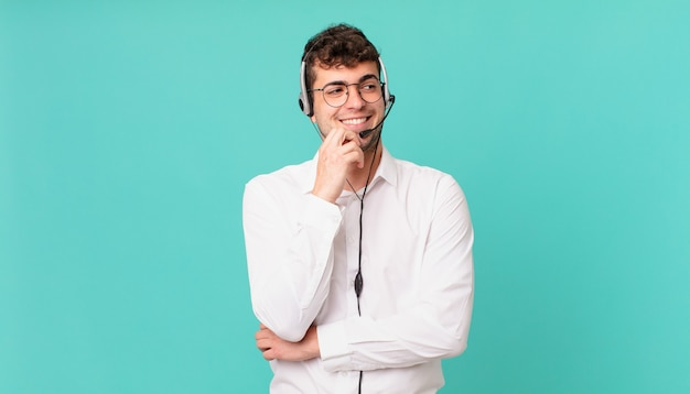 Operador de telemarketing sorrindo com uma expressão feliz e confiante com a mão no queixo, pensando e olhando para o lado