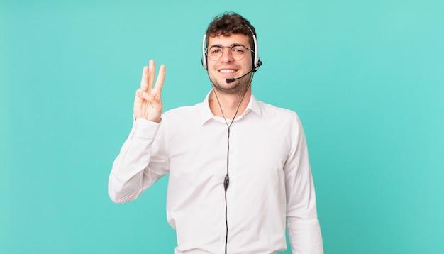 Operador de telemarketing sorrindo e parecendo amigável, mostrando o número três ou terceiro com a mão para a frente, em contagem regressiva