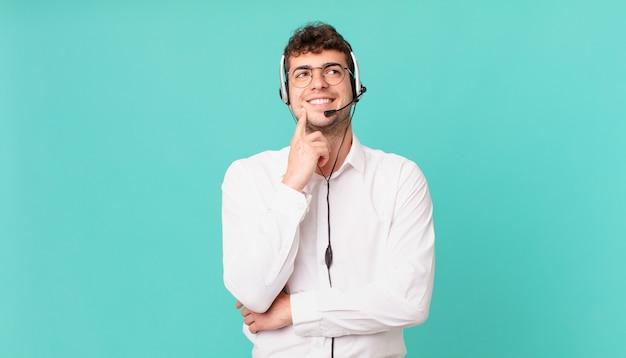 Operador de telemarketing sorrindo feliz e sonhando acordado ou duvidando, olhando para o lado