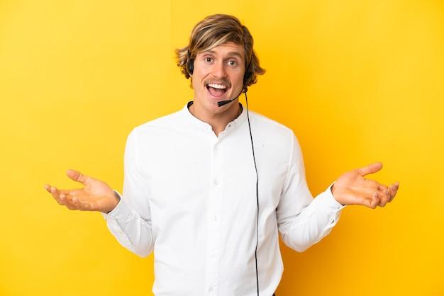 Operador de telemarketing trabalhando com um fone de ouvido isolado em amarelo com expressão facial chocada