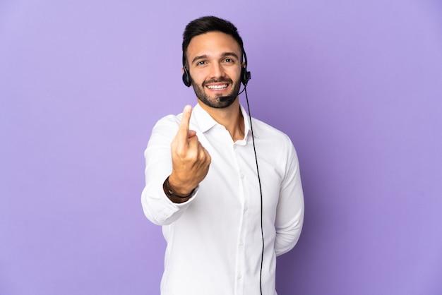 Operador de telemarketing trabalhando com um fone de ouvido isolado em um fundo roxo, fazendo um gesto próximo