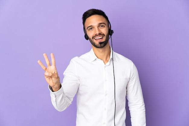 Operador de telemarketing trabalhando com um fone de ouvido isolado em um fundo roxo feliz e contando três com os dedos