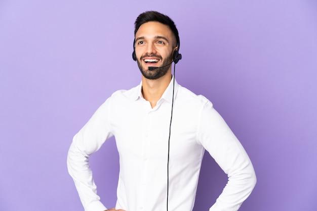 Operador de telemarketing trabalhando com um fone de ouvido isolado em um fundo roxo, posando com os braços no quadril e sorrindo