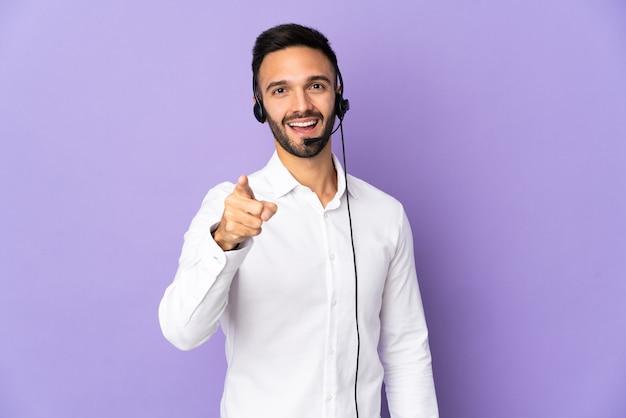 Operador de telemarketing trabalhando com um fone de ouvido isolado em um fundo roxo surpreso e apontando para a frente