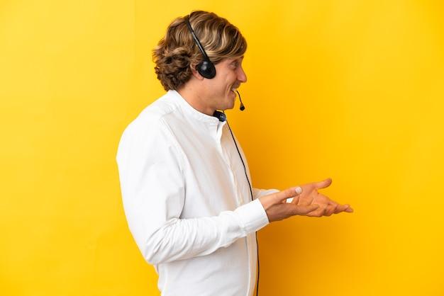 Operador de telemarketing trabalhando com um fone de ouvido isolado na parede amarela com expressão de surpresa enquanto olha para o lado