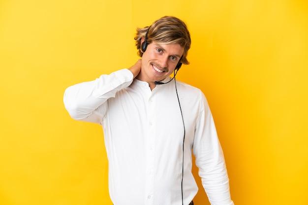 Operador de telemarketing trabalhando com um fone de ouvido isolado na parede amarela rindo