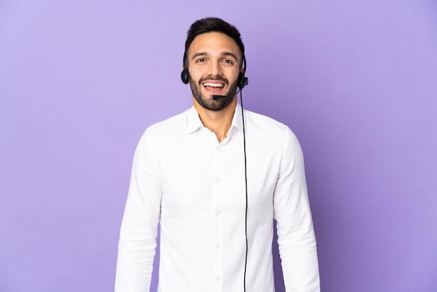 Operador de telemarketing trabalhando com um fone de ouvido isolado na parede roxa com expressão facial surpresa