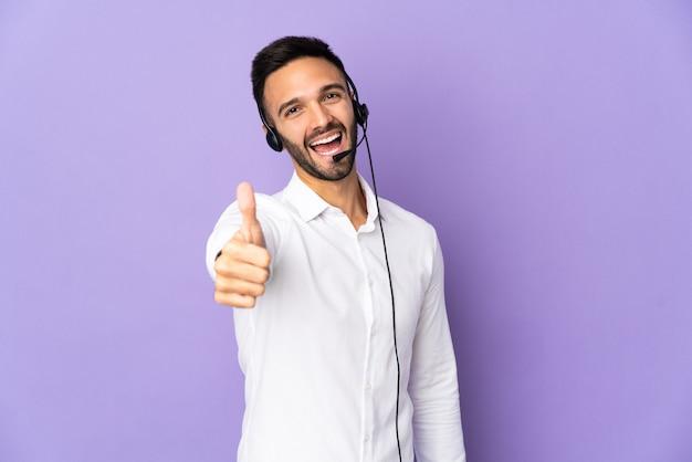 Operador de telemarketing trabalhando com um fone de ouvido isolado na parede roxa com o polegar para cima porque algo bom aconteceu