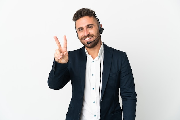Operador de telemarketing trabalhando com um fone de ouvido isolado no branco, sorrindo e mostrando sinal de vitória