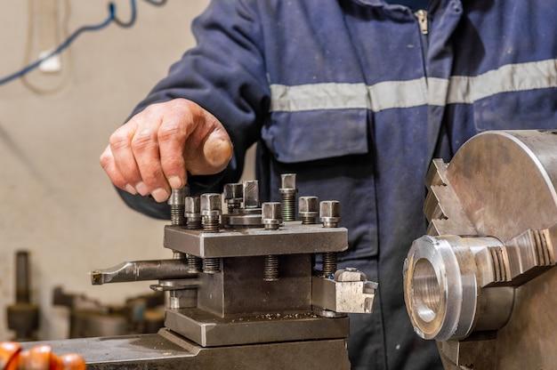Operador de trabalhador industrial pesado trabalhando com torno mecânico