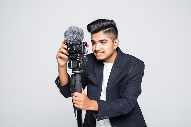 Operador indiano novo da câmara de vídeo do homem isolado no fundo branco.