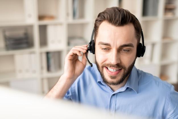 Operador jovem e amigável com fone de ouvido, explicando algo para um dos clientes online enquanto olha para a tela do computador