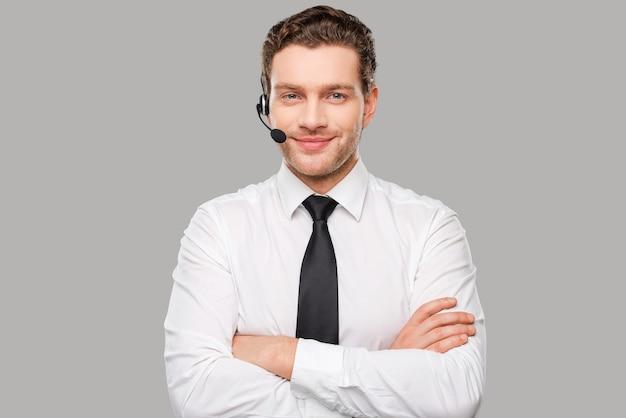 Operador masculino. jovem bonito em trajes formais e fone de ouvido, olhando para a câmera e sorrindo em pé contra um fundo cinza