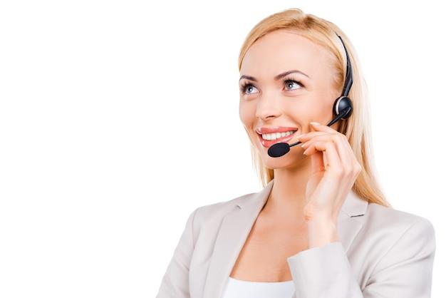Operador no trabalho. representante de atendimento ao cliente maduro e confiante ajustando seu fone de ouvido e sorrindo enquanto fica de pé contra um fundo branco