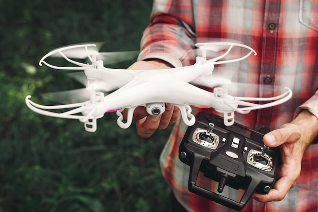 Operador segurando o controle remoto e quadrocopter.