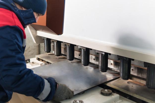 Operador trabalhando corte e dobra de folha de metal por máquina de dobra de chapa de alta precisão