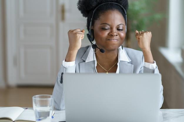 Operadora de serviço de suporte animada, mulher negra torcendo por boas notícias, olhar laptop sentar na mesa