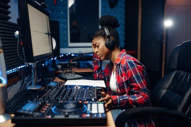 Operadora de som feminina em estúdio de gravação de áudio
