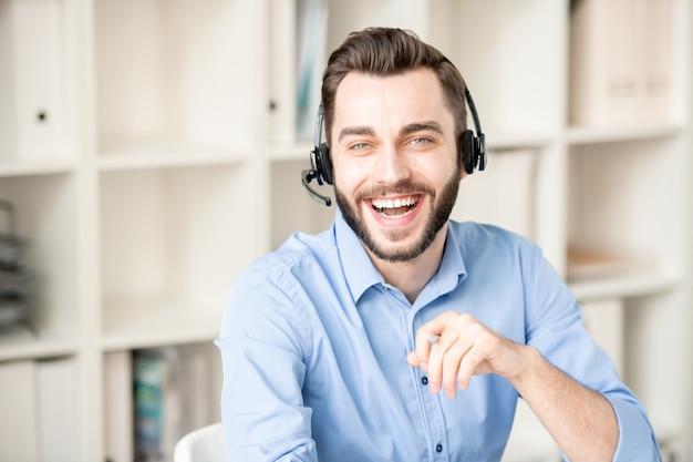 Operadora de sucesso jovem rindo com fone de ouvido sentado no escritório e se comunicando com clientes online