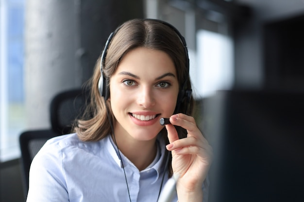 Operadora de suporte ao cliente feminino com fone de ouvido e sorrindo.