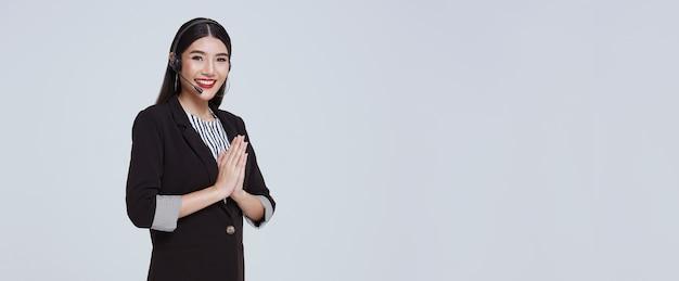 Operadora de telefone de suporte ao cliente de empresária asiática sorridente com cultura tailandesa sawasdee