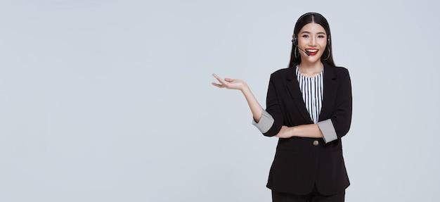 Operadora de telefone de suporte ao cliente de empresária asiática sorridente isolada sobre fundo cinza
