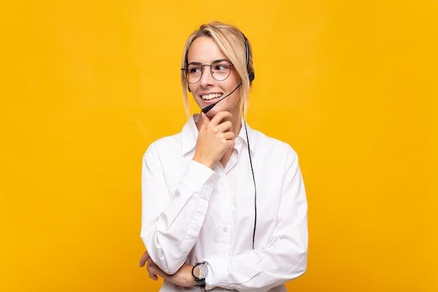 Operadora de telemarketing jovem sorrindo com uma expressão feliz e confiante com a mão no queixo, pensando e olhando para o lado