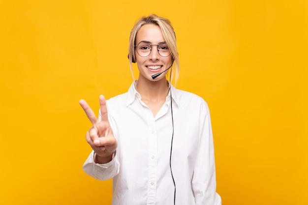 Operadora de telemarketing jovem sorrindo e parecendo amigável, mostrando o número dois ou o segundo com a mão para a frente, em contagem regressiva