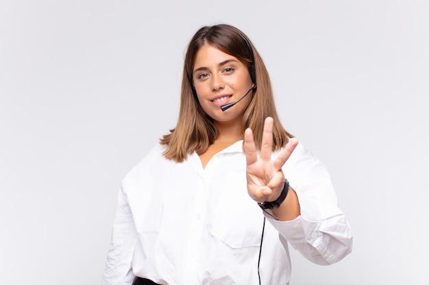Operadora de telemarketing jovem sorrindo e parecendo amigável, mostrando o número três ou terceiro com a mão para a frente, em contagem regressiva