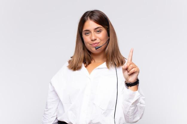 Operadora de telemarketing jovem sorrindo e parecendo amigável, mostrando o número um ou primeiro com a mão para a frente, em contagem regressiva Foto Premium