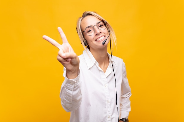 Operadora de telemarketing jovem sorrindo e parecendo feliz, despreocupada e positiva, gesticulando vitória ou paz com uma das mãos